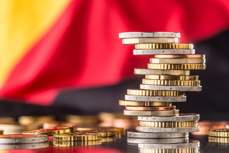 Plan de relance Allemagne symbolisé par une piles d'euros avec dans l'arrière-plan le drapeau allemand